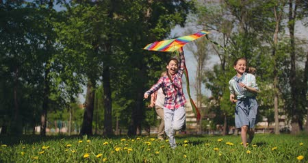 Three happy little friends flying a kite in park 影像素材