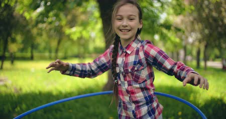 abroncs : Happy little girl spinning the hoop and smiling at camera