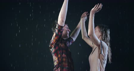 Cheerful young couple having fun in rain 影像素材