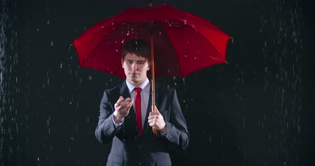 стоять : Young man with red umbrella reaching out his hand to touch cold raindrops