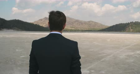sucho : Rear view of businessman in suit walking in desert Dostupné videozáznamy