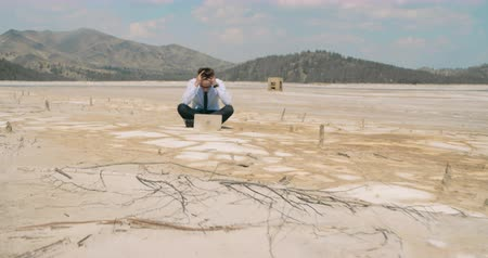 problem : Frustrated businessman sitting on cracked ground in dessert and trying to connect to Internet