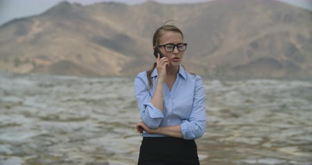 perdido : Confident businesswoman talking on cell phone in desert