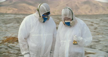 epidemia : Two shocked scientists in protective coveralls and masks collecting samples in infected zone Vídeos