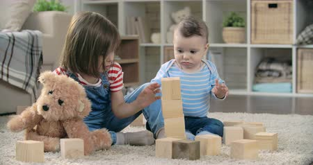 uczenie się : Cute children learning to stack toy blocks together