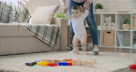 ilk : Young mother teaching her adorable baby son to walk and play with toy blocks