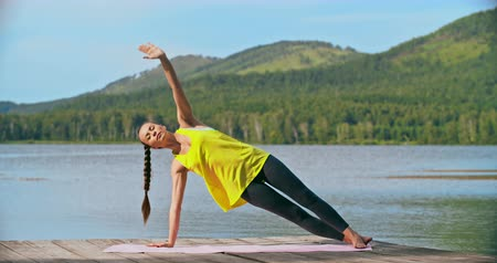 баланс : Young woman performing plank poses against a background of lake and mountains Стоковые видеозаписи