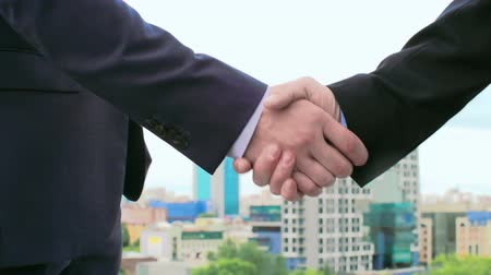 partnerstwo : Close-up of business handshake against city background