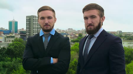 стоять : Video portrait of twin siblings in suits looking fixedly at camera against a city background