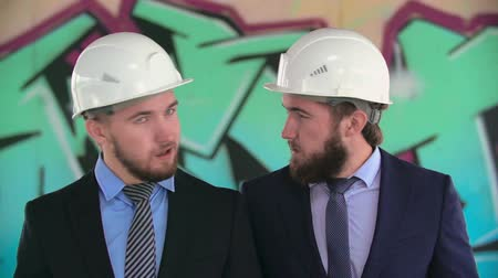 atenção : Close-up of two twin architects in helmets shaking heads in slow motion Stock Footage