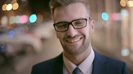 детеныш : Young businessman in eyeglasses turning his head towards the camera and giving a smile