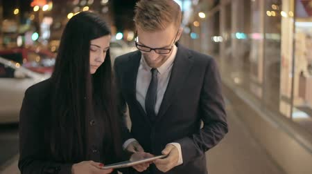 таблетка : Young couple using digital tablet in street at night in slow motion