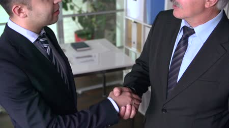 kezek : Tilt shot of two business partners talking and shaking hands at office