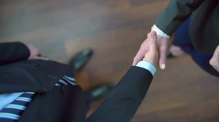 corporate : High angle view of mature business partners shaking hands in slow motion