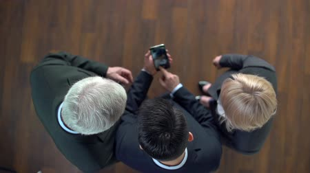 três pessoas : Group of business people looking at pictures on smartphone