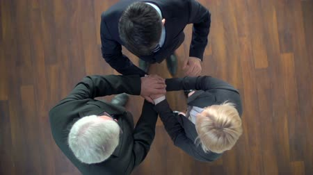három ember : Directly above view of mature business team stacking hands, raising arms up and smiling at camera Stock mozgókép
