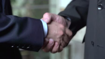 human hand : Tilt down of two businessmen shaking hands in slow motion Stock Footage