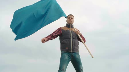 bandeira : Tilt up of young man with blue flag standing on the mountain top and celebrating his success