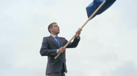 peak : Tilt up of young businessman in suit climbing a mountain and waving a blue flag on the top Stock Footage