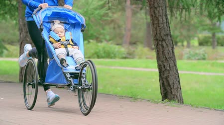 toló : Cropped woman running with her baby son sleeping in a jogging stroller