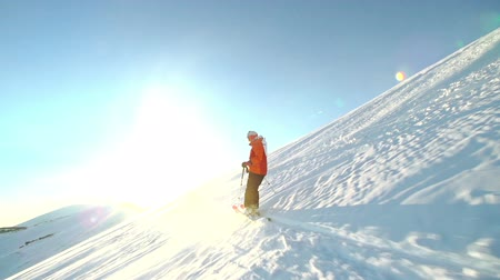 lesiklás : Tracking shot of a skier riding down the slope in sunlight