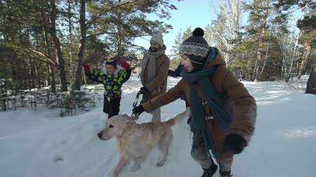 neve : Joyful family of four and their dog running through a winter park