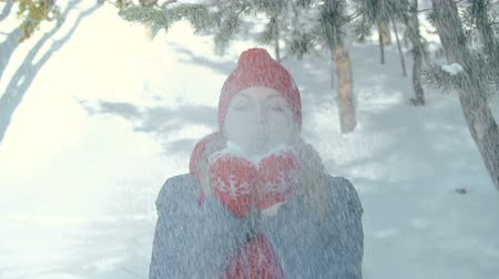 mittens : Beautiful woman blowing snow out of her hands and smiling at camera Stock Footage