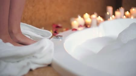 джакузи : Woman taking her bathrobe off and dipping her foot into a foamy hot tub Стоковые видеозаписи