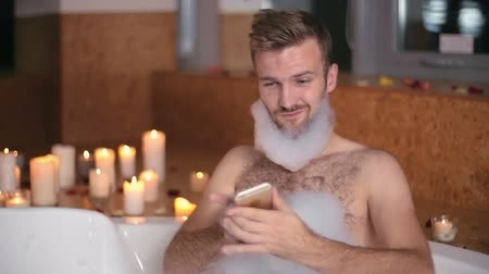 wanna : Handsome man taking a selfie in the bathtub with soap foam on his beard