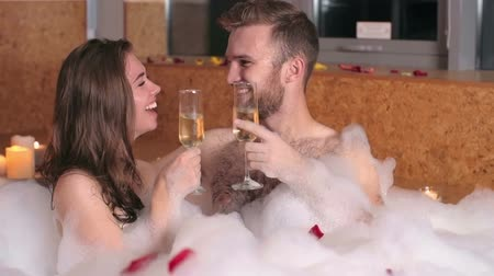 медовый месяц : Happy beautiful couple drinking champagne and kissing in bubble bath
