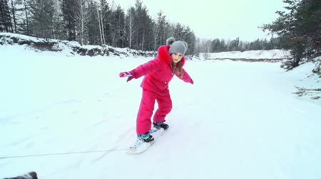 patim : Little girl balancing on a snowskate pulled on a leash