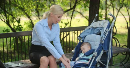 мама : Busy businesswoman working on laptop, answering cell phone and caring for her baby son in park Стоковые видеозаписи