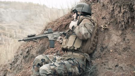 asker : Soldier hiding in a trench and using a portable radio set Stok Video
