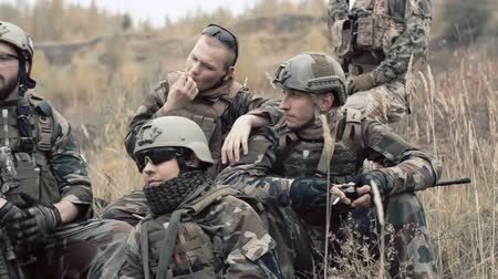 rests : Soldiers taking a rest during an assault, smoking and discussing a strategy