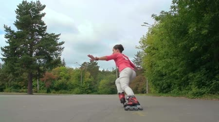 patim : Young woman practicing inline skating and performing a lunge in super slow motion