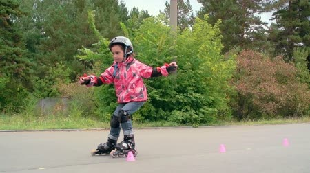 inline skating : Little girl roller skating between cones in slow motion