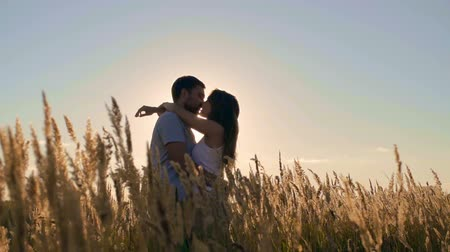 Lovely couple kissing in meadow of golden barley
