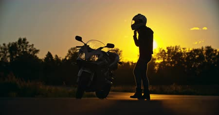 motocykl : Lady putting on motorcycle helmet and starting to ride at sunset Wideo