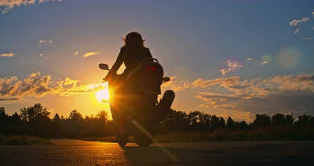 motocykl : Businesswoman starting up her motorcycle and riding away towards sunset