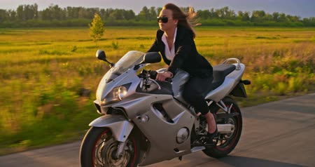 kaland : Follow shot of businesswoman riding her motorbike