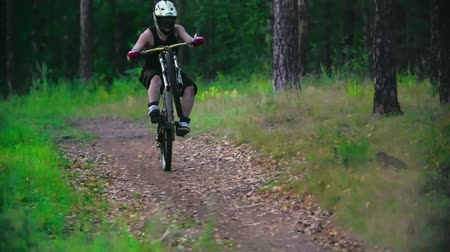 lesiklás : Rider back wheeling on his downhill bike down a forest trail