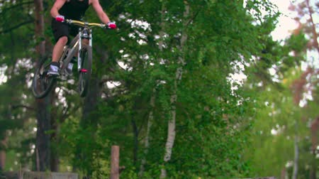экстремальный : Man on mountain bike jumping downhill in forest