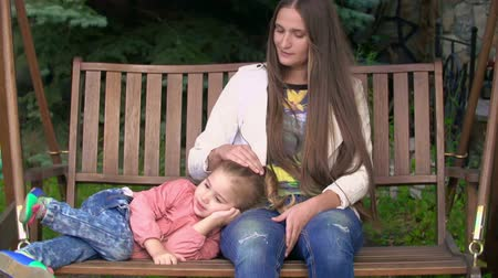 houpavý : Loving mother stroking a head of her cute little daughter on a swing bench