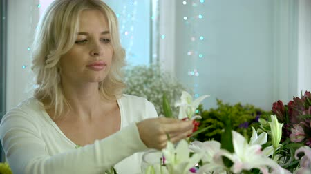 bouquets : Attractive floral designer making a composition of white lily flowers and smiling at camera Stock Footage