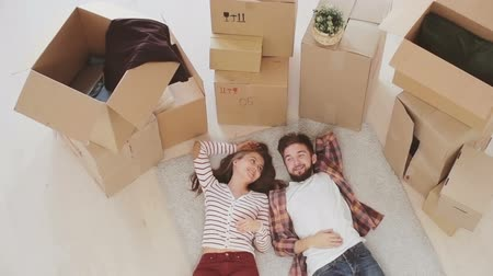 nowe mieszkanie : Happy couple lying down on the floor and sharing interior ideas