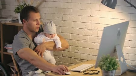 guy home : Young father rocking his adorable baby son while working on computer at home