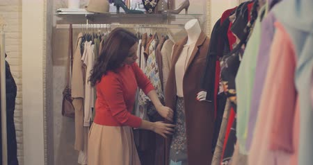 asistan : Shop assistant dressing mannequin and checking if everything is good on racks Stok Video