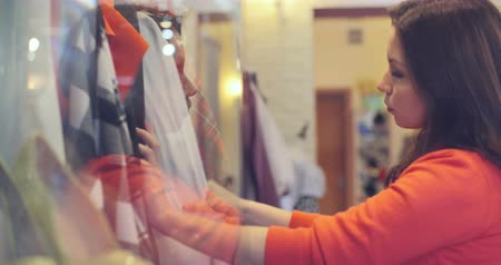 butik : Pretty young lady choosing blouse in fashion store