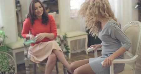pięta : Two beautiful women choosing perfect pair of shoes together
