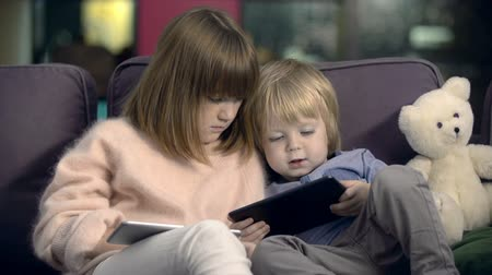 родной брат : Adorable little brother and sister sitting on the sofa together and using their tablets Стоковые видеозаписи